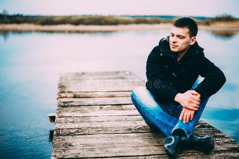 Jonge knappe mensenzitting op houten pijler, het ontspannen, het denken, het luisteren Toevallige stijl - jeans, jasje royalty-vrije stock foto