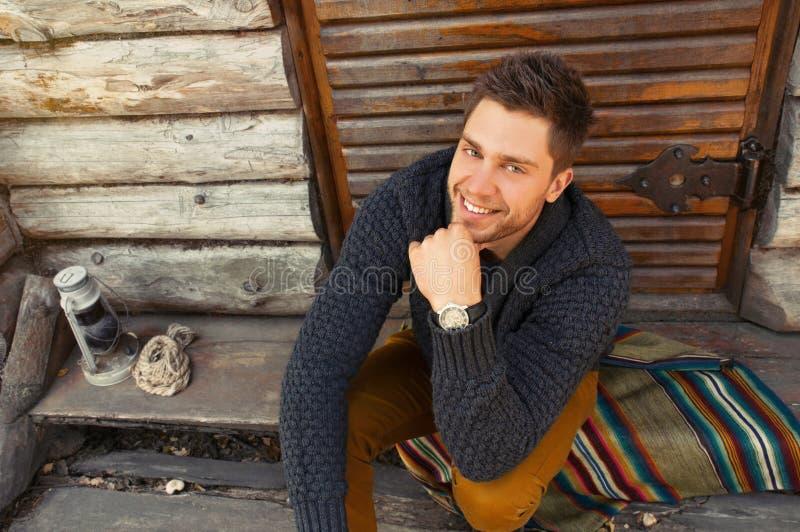 Jonge knappe modieuze mens door het houten coutry huis backgr stock foto's