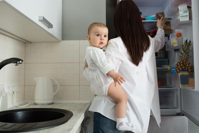 Jonge knappe moeder met donker haar die pasgeboren zoon op handen houden en babyvoedsel in geopende ijskast zoeken stock afbeeldingen