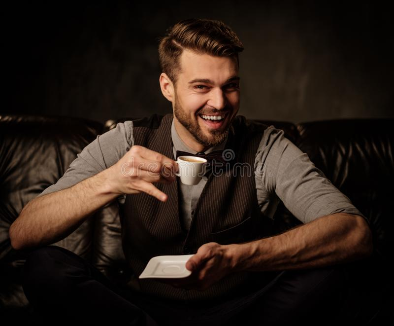 Jonge knappe ouderwetse gebaarde mens die pret met kop van koffie op comfortabele leerbank hebben op donkere achtergrond royalty-vrije stock foto