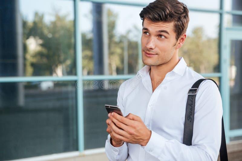 Jonge knappe peinzende zakenman die mobiele telefoon met behulp van stock foto
