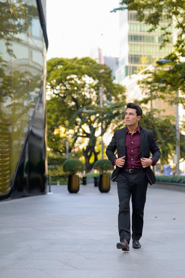 Jonge knappe Spaanse zakenman die buiten het bureaugebouw lopen stock foto