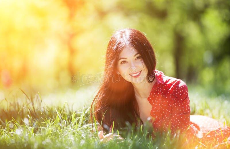 Jonge knappe vrouw in rode jurk die ontspannend is in het park Schoonheid, natuur met kleurrijke achtergrond, bomen in het zomers royalty-vrije stock fotografie