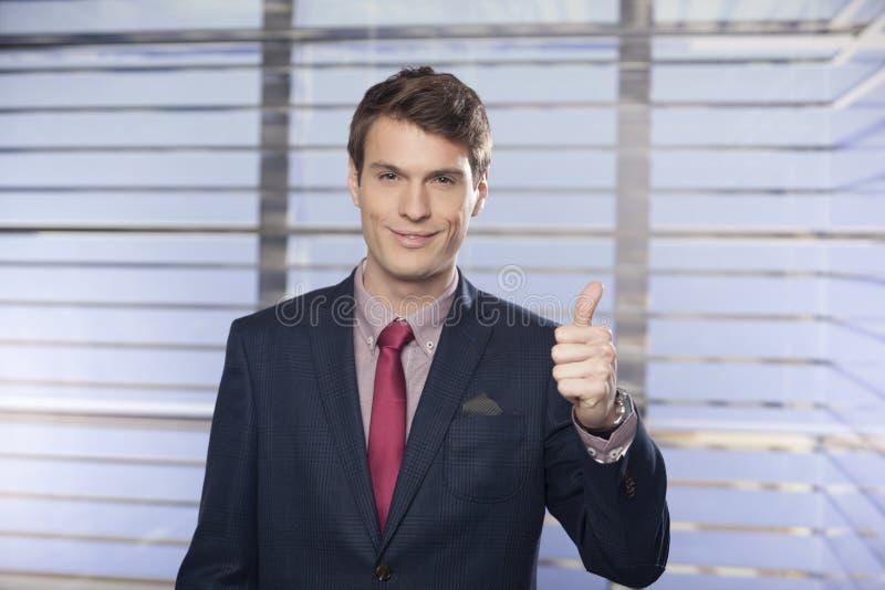 Jonge knappe zakenlieden die duim-omhoog in het bureau tonen royalty-vrije stock fotografie