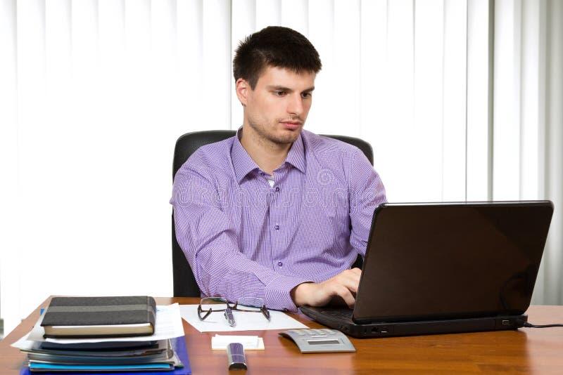 Jonge knappe zakenman die aan laptop werken stock afbeelding