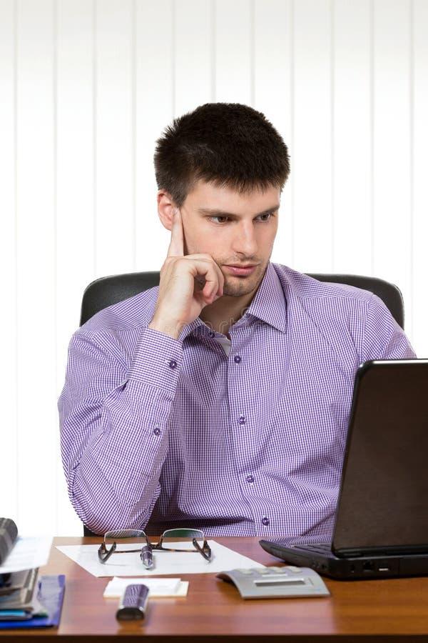 Jonge knappe zakenman die aan laptop werken royalty-vrije stock afbeeldingen
