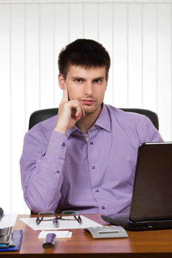 Jonge knappe zakenman die aan zijn bureau werken stock foto's
