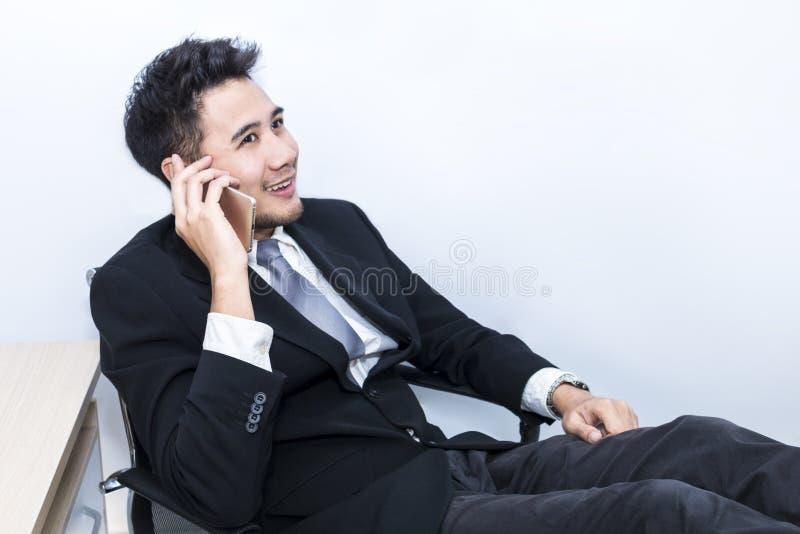Jonge knappe zakenman die en met telefoon op kantoor glimlachen spreken royalty-vrije stock fotografie