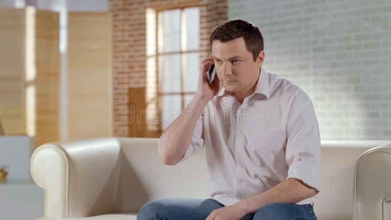 Jonge knappe zakenman die ernstig telefoongesprek met partner hebben stock foto's