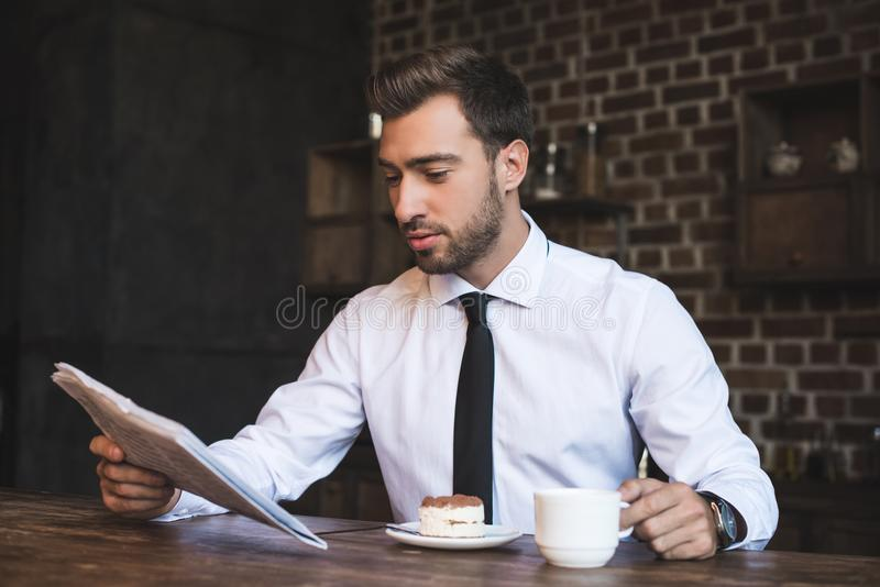 Jonge knappe zakenman in formele slijtagezitting bij koffiewinkel en lezing stock foto's