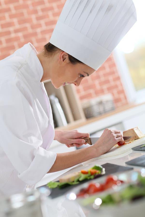 Jonge kok die voorgerechten voorbereiden stock foto