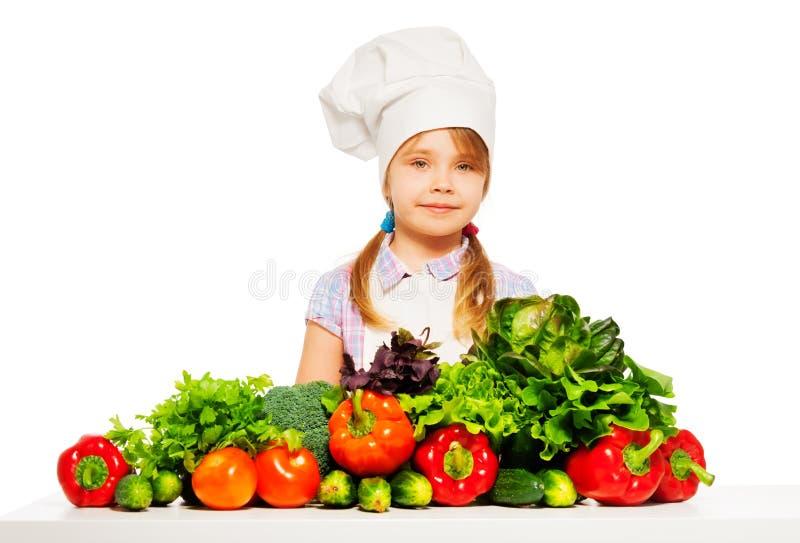 Jonge kok in eenvormig met verse groenten stock fotografie