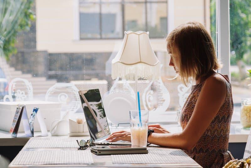 Jonge kortharige vrouw die laptop in koffie met behulp van stock afbeeldingen