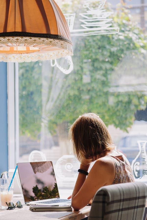 Jonge kortharige vrouw die laptop in koffie met behulp van royalty-vrije stock foto