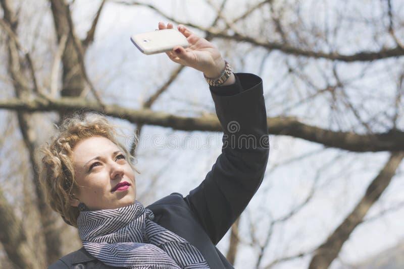 Jonge krullende blonde vrouw die beeld van zich nemen stock foto's
