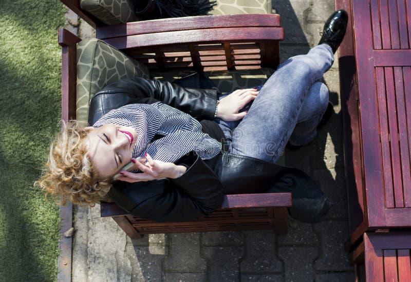 Jonge krullende blonde vrouw die op de telefoon in koffie spreken royalty-vrije stock foto
