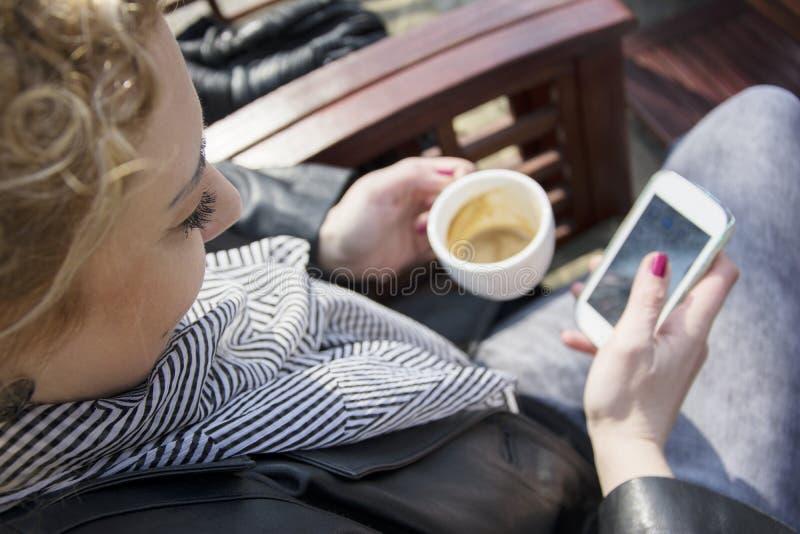 Jonge krullende blonde vrouw het drinken koffie en het typen op de telefoon royalty-vrije stock foto's