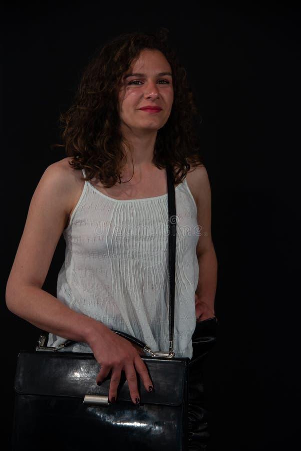 Jonge krullende donkerbruine vrouw met zwarte schouderzak stock afbeelding