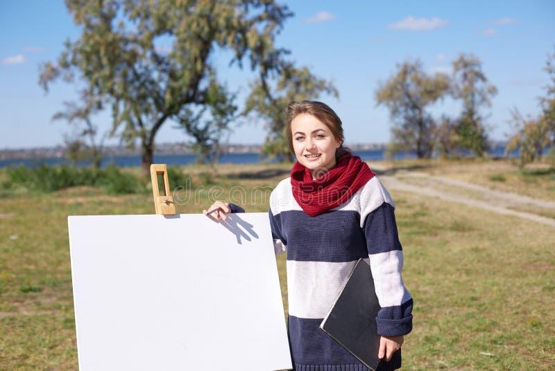 Jonge kunstenaar die een de herfstlandschap op de aardachtergrond schilderen Het concept van de kunst Wit masker met rode vlek va royalty-vrije stock foto's