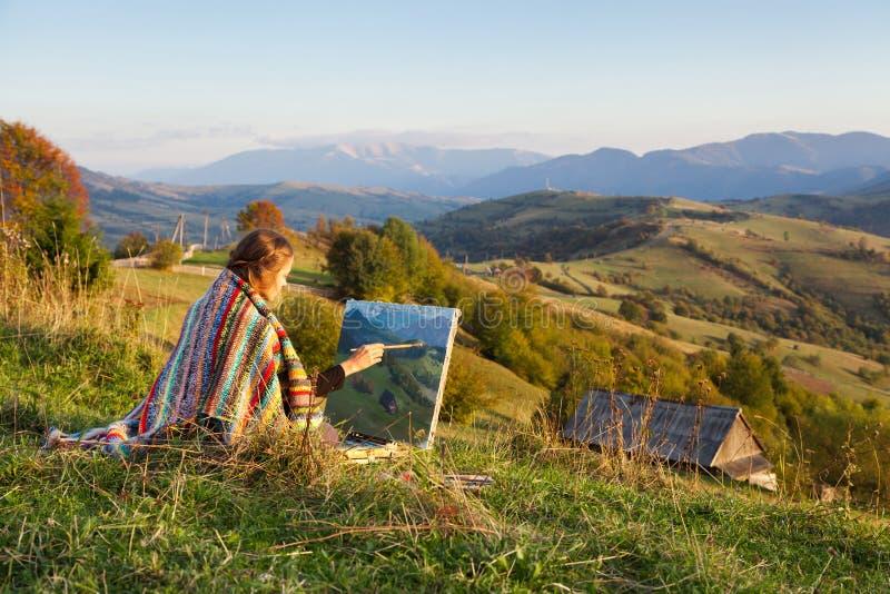 Jonge kunstenaar die een de herfstlandschap schildert stock foto's