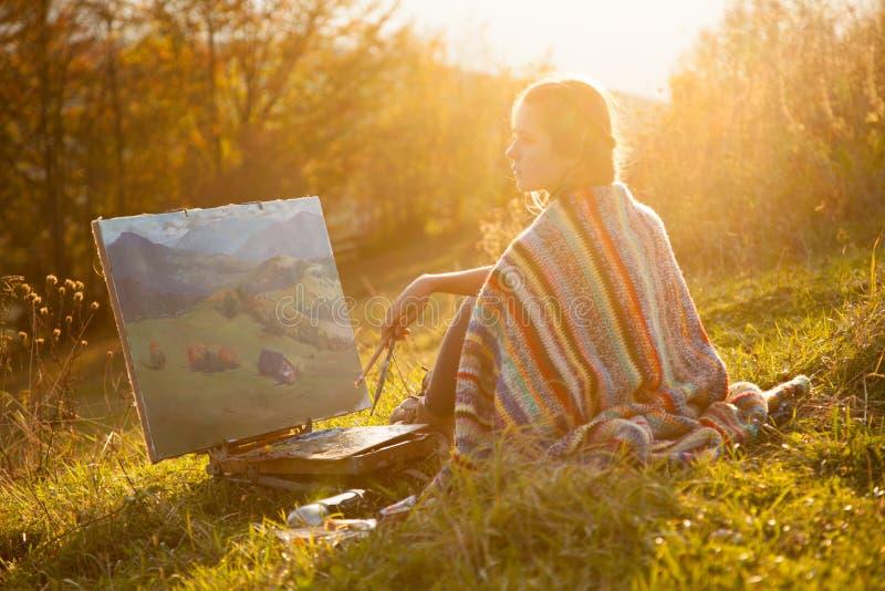 Jonge kunstenaar die een landschap schilderen stock foto