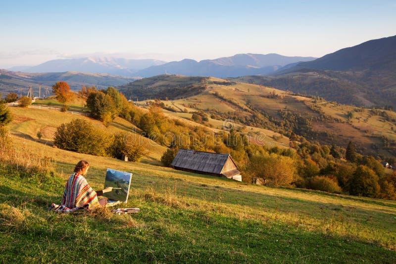 Jonge kunstenaar die een landschap schildert stock foto's