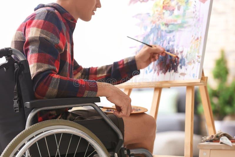 Jonge kunstenaar in rolstoel het schilderen beeld thuis stock afbeeldingen