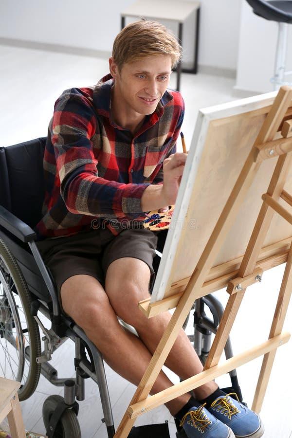 Jonge kunstenaar in rolstoel het schilderen beeld thuis royalty-vrije stock fotografie