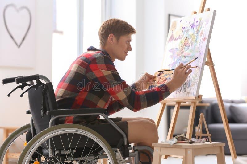 Jonge kunstenaar in rolstoel het schilderen beeld thuis royalty-vrije stock afbeelding