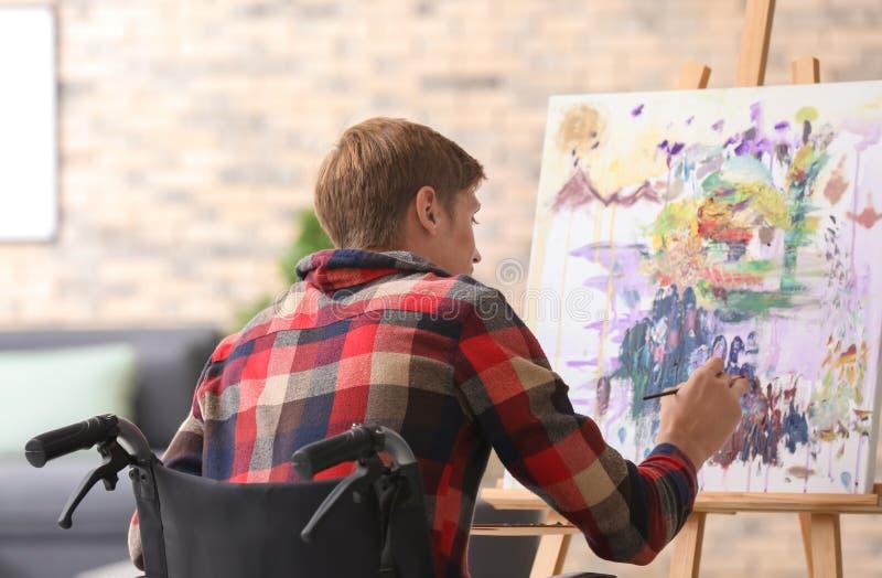 Jonge kunstenaar in rolstoel het schilderen beeld thuis royalty-vrije stock foto