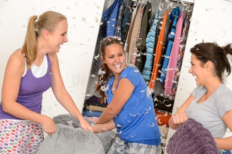 Jonge lachende meisjes tijdens hoofdkussenstrijd royalty-vrije stock afbeeldingen