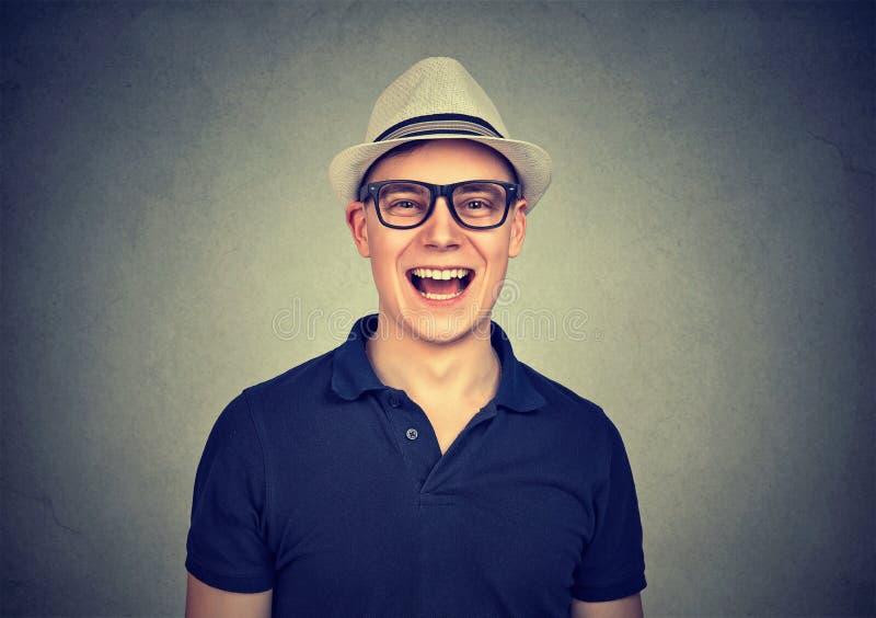 Jonge lachende mens met hoed en glazen stock afbeeldingen