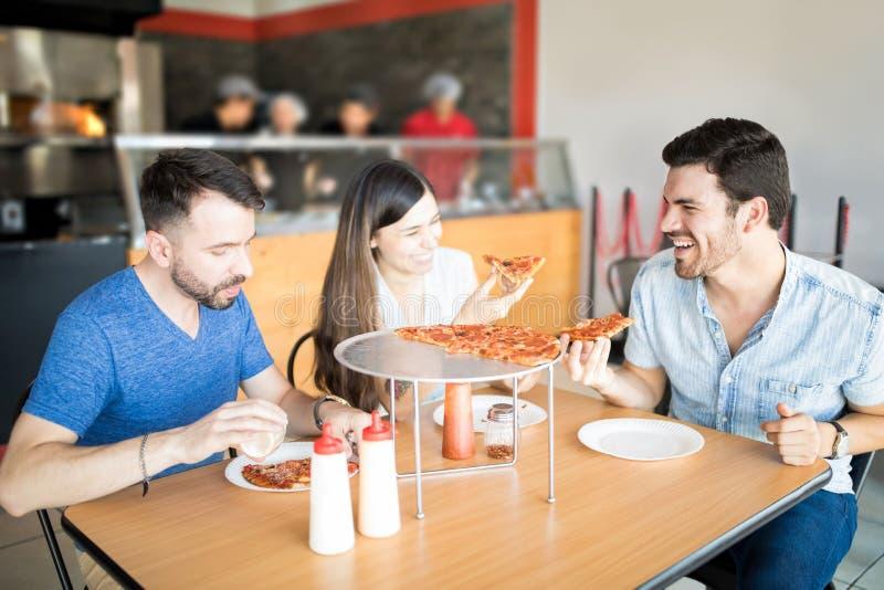 Jonge lachende vrienden die pizza eten en pret hebben stock fotografie