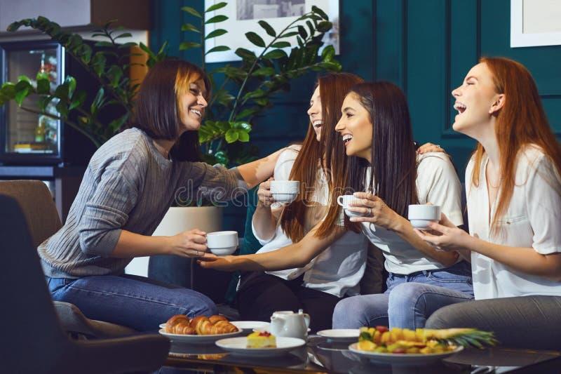 Jonge lachende vrouwen die theekransje hebben stock afbeeldingen
