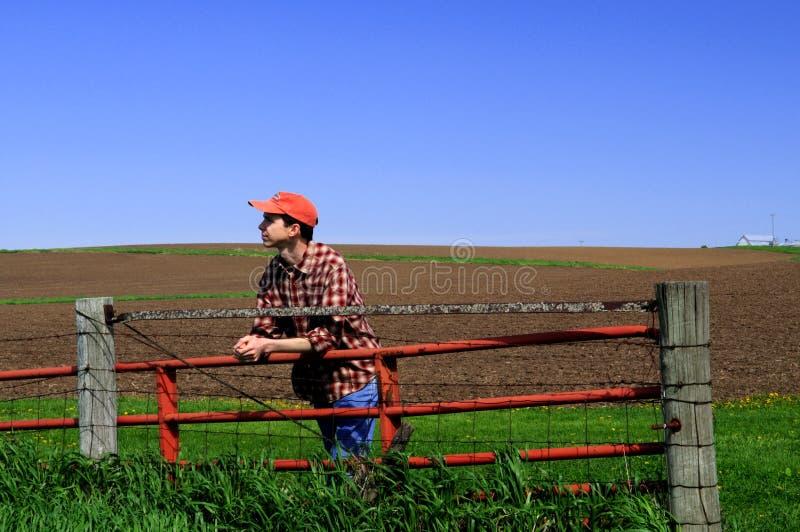 Jonge landbouwer bij de poort. royalty-vrije stock afbeeldingen