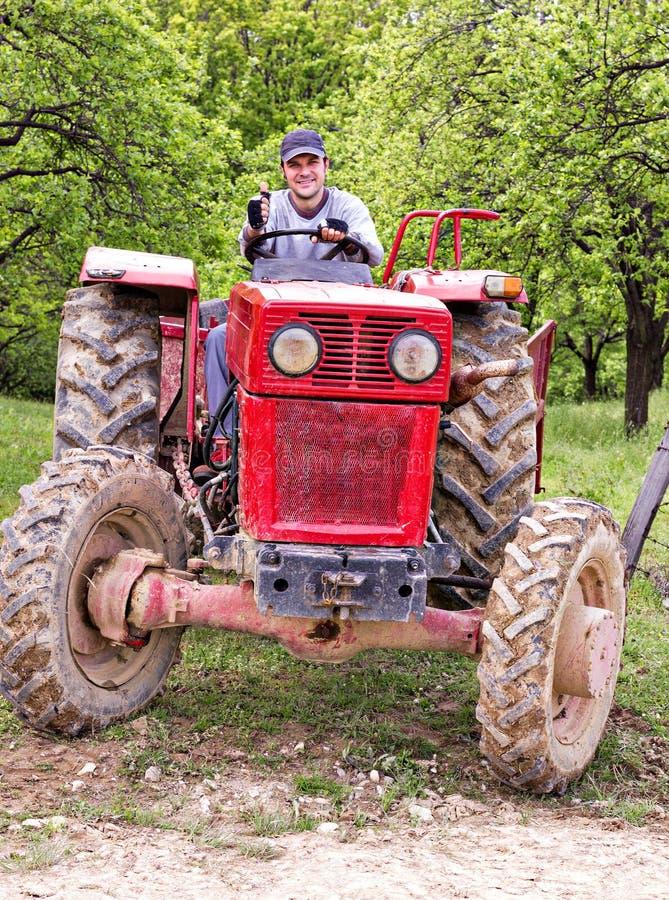 Jonge landbouwer die zijn tractor drijven royalty-vrije stock afbeeldingen