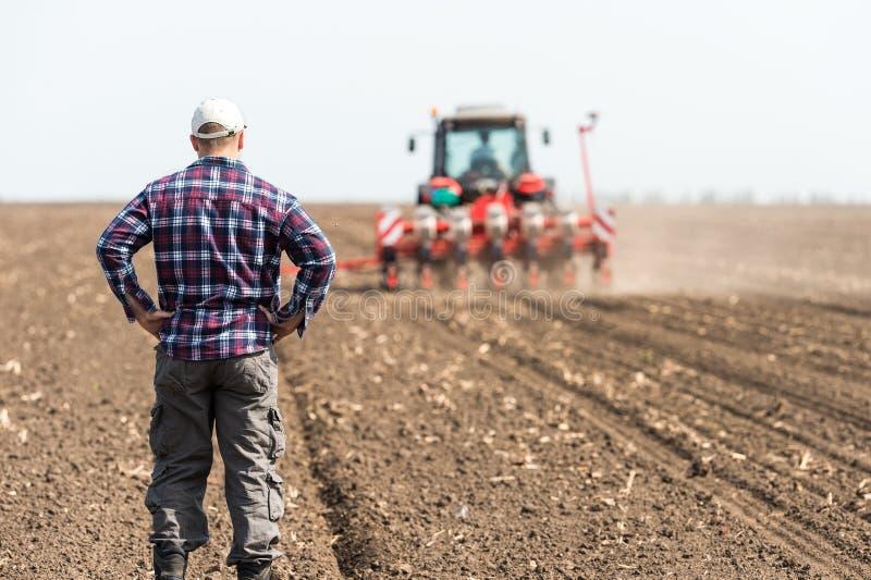 Jonge landbouwer op landbouwgrond stock foto's