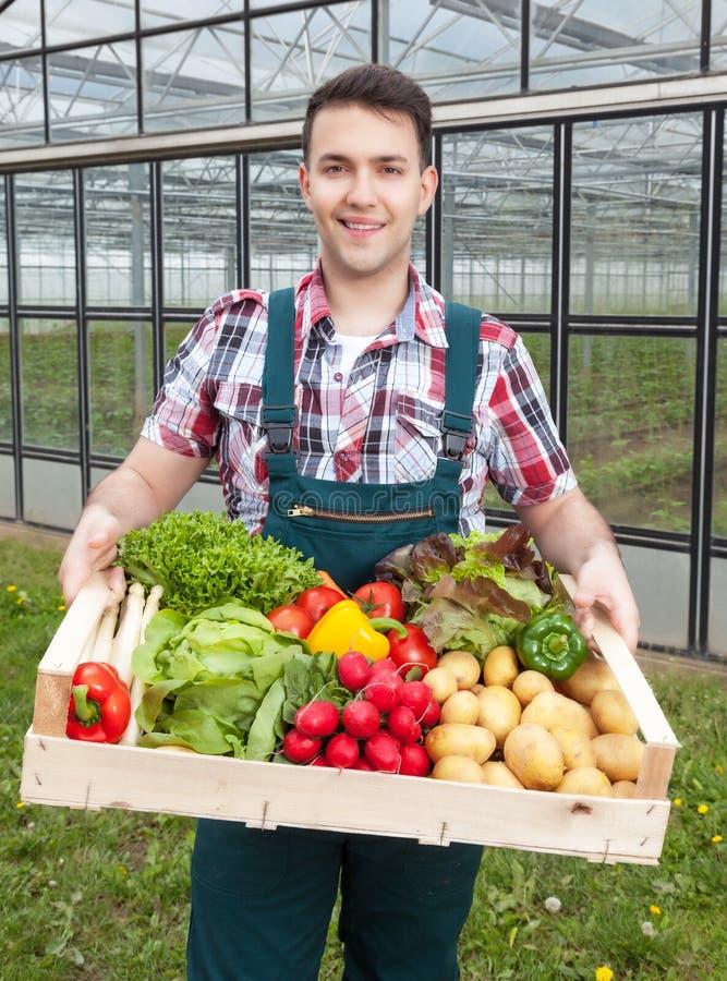 Jonge landbouwer voor een serre met groenten stock afbeelding