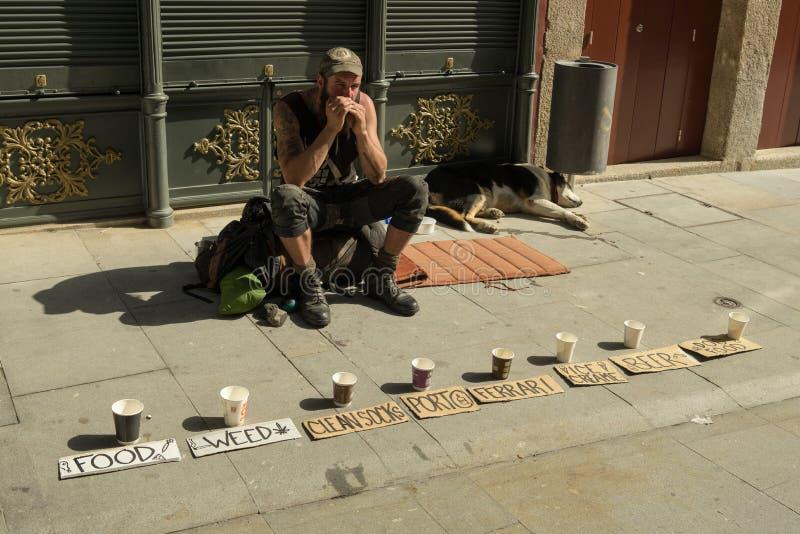 Jonge landloper die om geld in straten van Porto vragen stock foto's