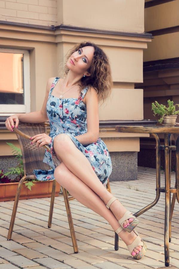 Jonge langbenige vrouwenzitting in een rieten koffie van de stoelstraat Zij glimlacht, kijkt verzonden naar de camera Het dragen  royalty-vrije stock afbeelding