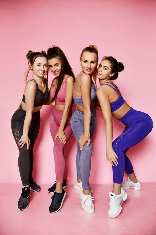 Jonge lange atletische vrouwen in blauwe, grijze, bruine status achter elkaar Geschiktheidsmeisjes die op roze achtergrond stelle royalty-vrije stock afbeeldingen