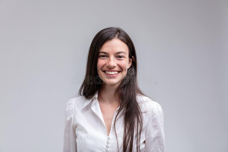 Jonge langharige glimlachende vrouw in wit overhemd royalty-vrije stock afbeelding