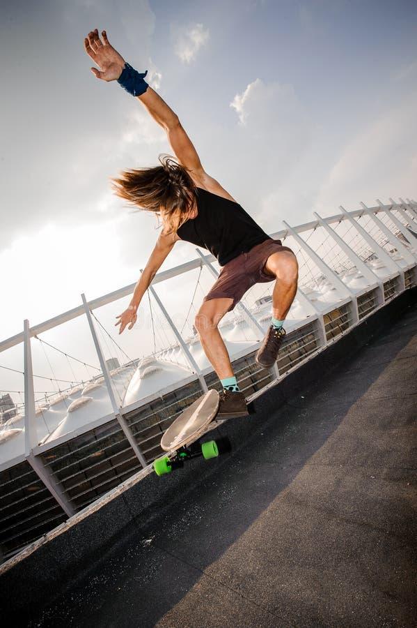 Jonge langharige kerel die hoog op een longboard springen stock afbeelding