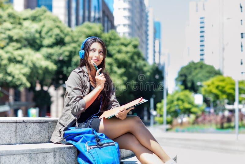Jonge Latijns-Amerikaanse vrouwelijke student met hoofdtelefoon in stad stock afbeelding