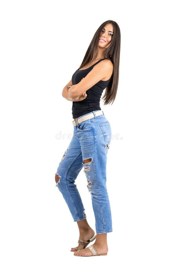 Jonge Latijnse gelukkige glimlachende vrouw die met gevouwen wapens camera bekijken stock foto's