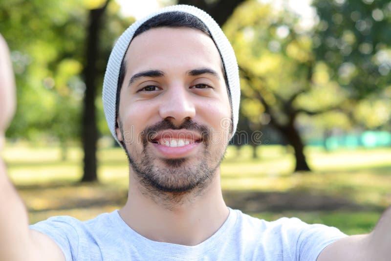 Jonge Latijnse mens die een selfie in een park nemen stock afbeeldingen