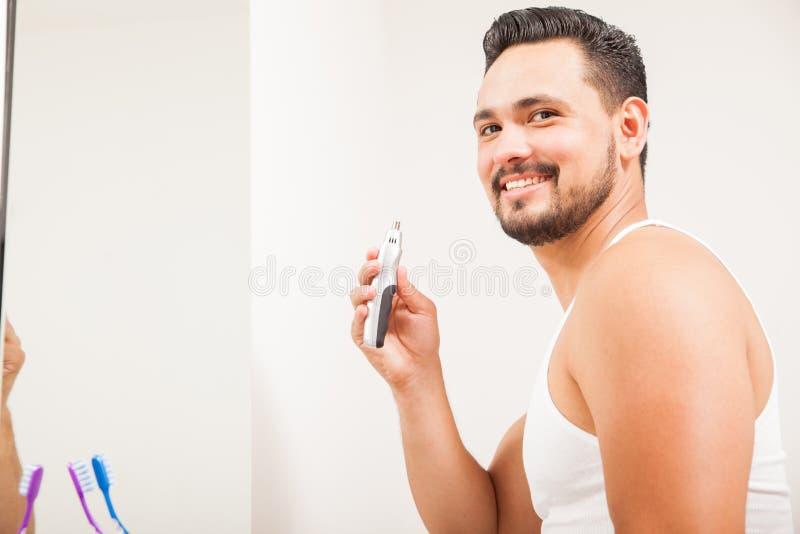 Jonge Latijnse mens die een snoeischaar van het neushaar met behulp van royalty-vrije stock foto's