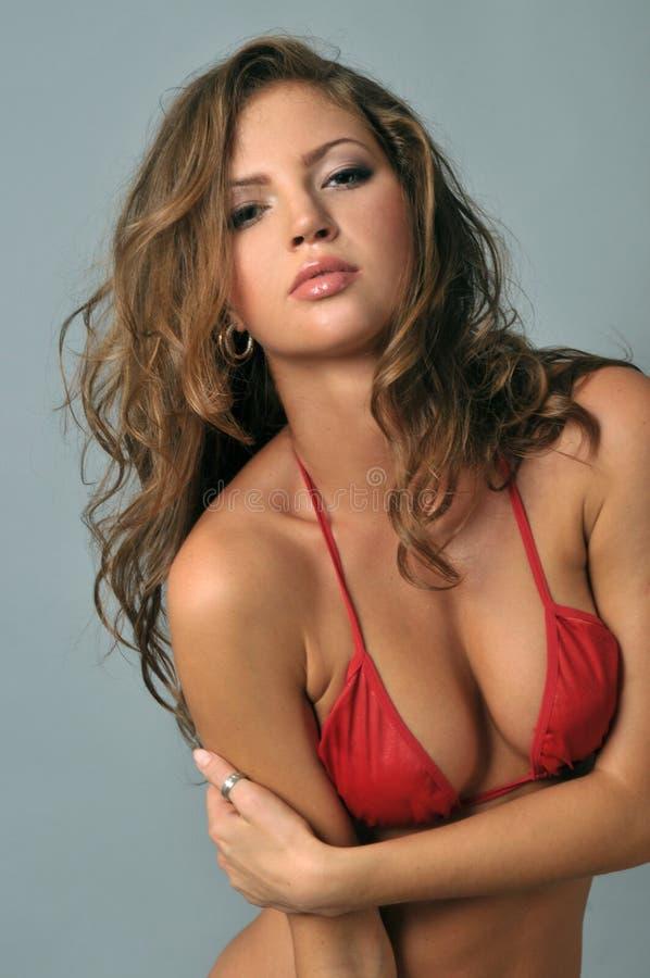 Jonge Latijnse vrouw in bikini sexy stellen stock fotografie