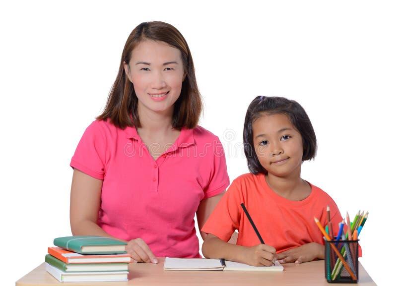 Jonge Leraar die kind met het schrijven van les helpen die op witte achtergrond wordt geïsoleerd stock fotografie