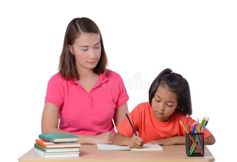 Jonge Leraar die kind met het schrijven van les helpen die op witte achtergrond wordt ge?soleerd royalty-vrije stock foto